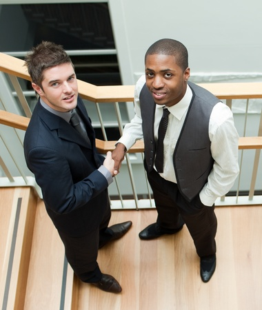 Two businessmen shaking hands on stairs and smiling at the camera photo
