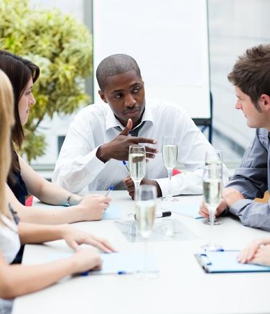 Ethnische Manager im Gespräch mit seinem Team mit Champagner Lizenzfreie Bilder - 10248023
