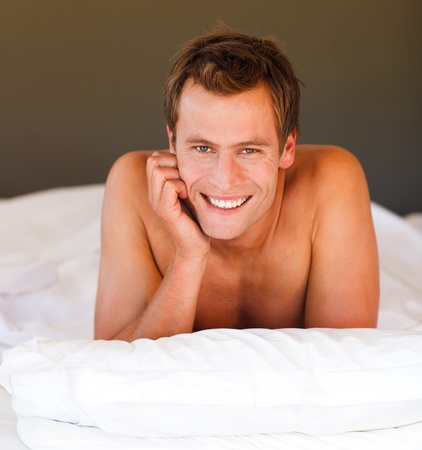 Attractive smiling youn boy in bed photo