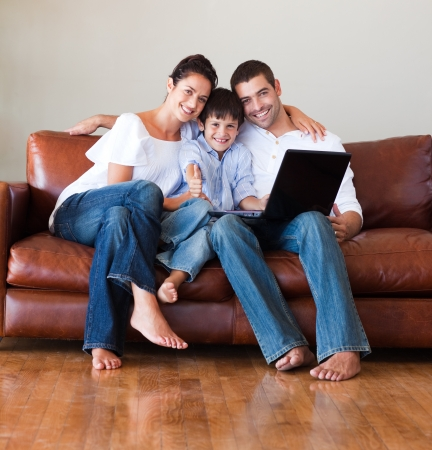 family on couch: Parents and kid using a laptop with thumbs up