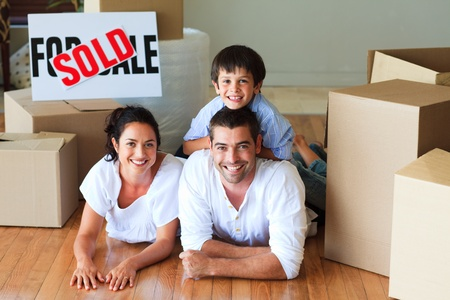 family moving house: Family in their new house lying on floor with boxes