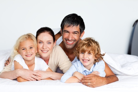 Lovely family lying on a bed