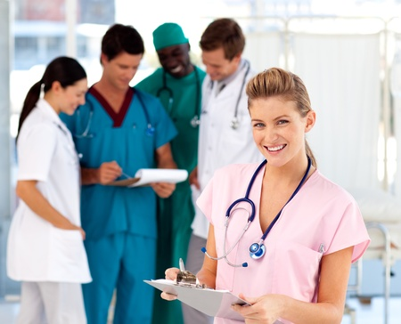Blonde nurse with her team in the background photo