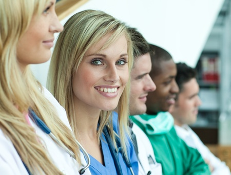 Portrait of female doctor smiling at the camera with her team in a line on stairs  photo