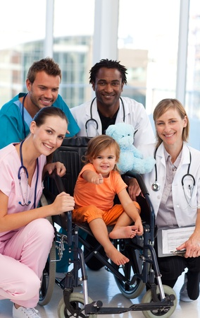 Baby Girl in a Wheelchair with �rzteteam Stockfoto
