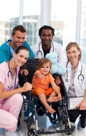 Baby meisje in een rolstoel met medisch team
