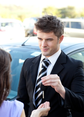 Young salesman giving car photo