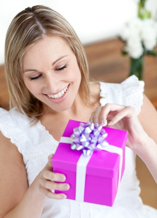 Delighted woman opening a gift sitting on the floor Stock Photo - 10249869