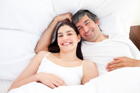 cuddling: Smiling couple hugging lying in their bed