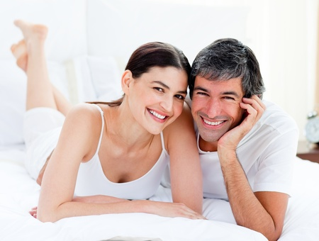 enamored: Enamored couple embracing lying on their bed