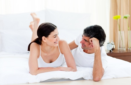 gratified: Affectionate couple interacting lying on their bed