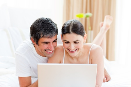 Affectionate couple using a laptop  photo