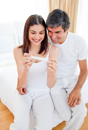 finding out: Smiling couple finding out results of a pregnancy test Stock Photo