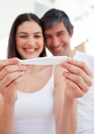 prueba de embarazo: Pareja alegre encontrar resultados de una prueba de embarazo