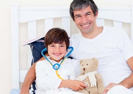 Cheerful father and his sick son playing with a stethoscope photo