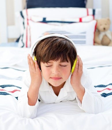 Adorable little boy listening music with headphones on  photo