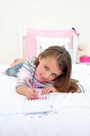 Cute Little girl writing on a notebook  photo