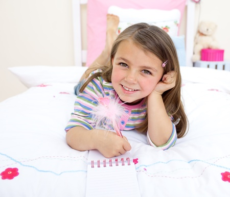 writing western: Smiling little girl playing on her bed