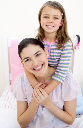Smiling little girl hugging her mother  photo
