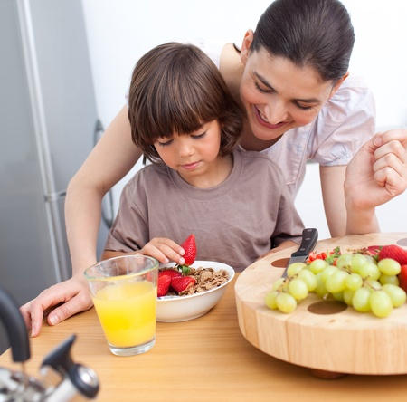 Jolly mother and her child having breakfast Stock Photo - 10247274