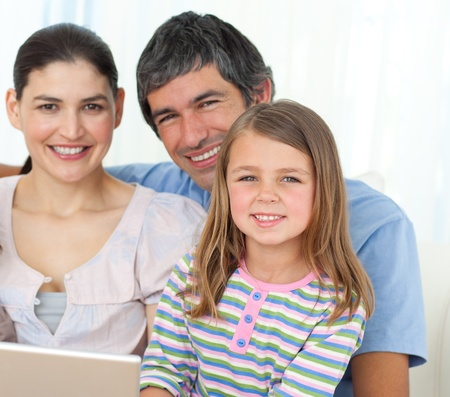 Little girl using a laptop with her parents  photo