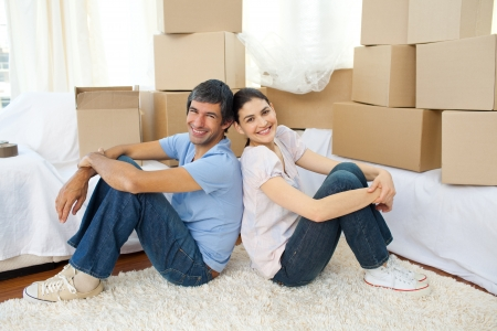moving house: Happy couple relaxing while moving house