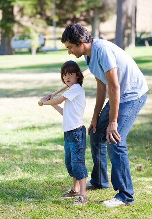 Happy father teaching baseball to his son photo