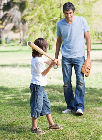 Cute little boy playing baseball with his father photo