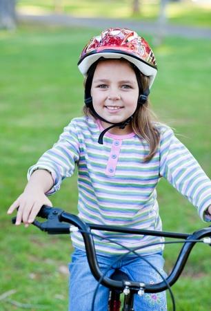 Joyful little girl riding a bike Stock Photo - 10248849