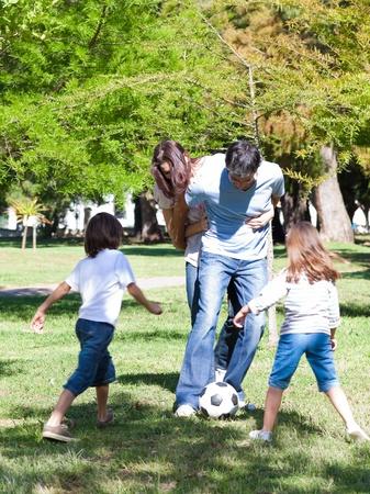 familia animada: Familia animada jugando al fútbol  Foto de archivo