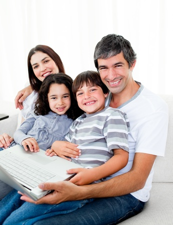 Jolly family using a laptop sitting on sofa photo