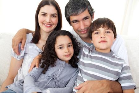 Retrato de una familia amorosa sentado en un sofá