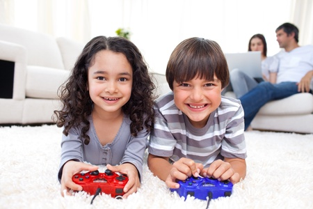 kids games: Smiling siblings playing video games lying on the floor Stock Photo