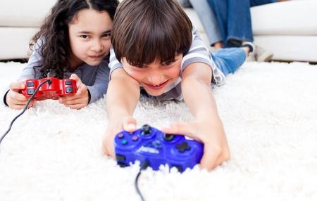 ni�os jugando videojuegos: Los ni�os alegres jugando juegos de video tendidos en el suelo