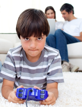 Concentrated boy playing video games lying on the floor  photo