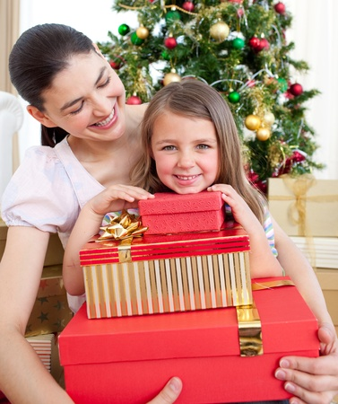 Mother and daughter at home holding a Christmas gift photo