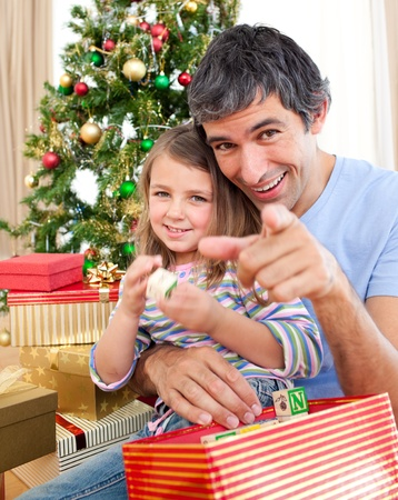 Father and little girl playing with Christmas presents photo