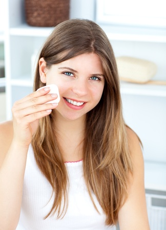 Smiling woman putting foundation cream against a white background  photo