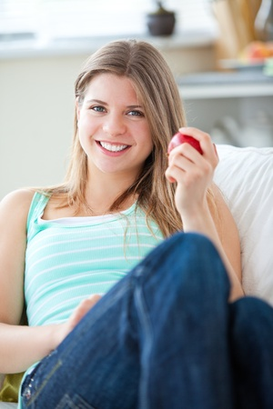 Beautiful woman eating an apple at home  photo