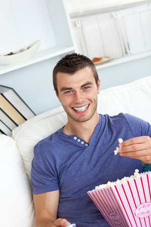 Handsome man eating popcorn on a sofa photo