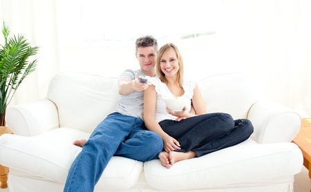 Adorable couple using a remote in the living-room Stock Photo - 10247910