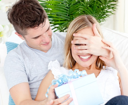 Young couple looking at the camera with a present in the living-room Stock Photo - 10248856