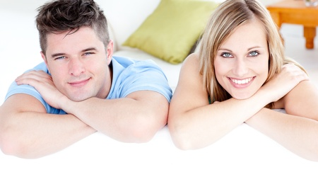 Affectionate couple looking at the camera on a sofa at home photo