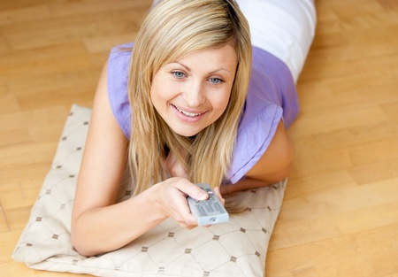 Smiling young woman watching TV lying on the floor at home  photo