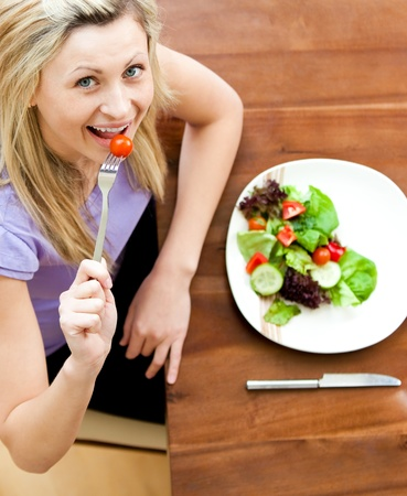 Portrait of a bright woman eating a salad in the living-room  Stock Photo - 10249155