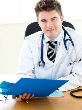 Self-assured doctor reading a report Stock Photo - 10250103