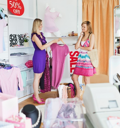 Teen women choosing clothes together photo
