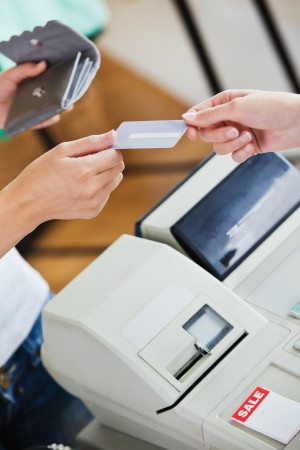 Close-up of a teen woman paying with her credit card photo