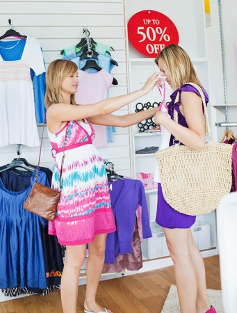 Cheerful women choosing clothes together photo