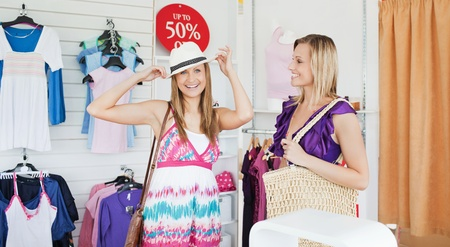 Smiling women choosing clothes together photo